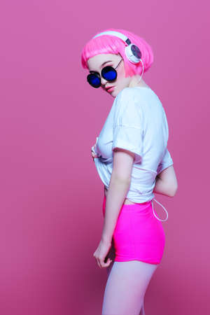Trendy girl with pink hair wearing sunglasses enjoys the music on headphones. Pink background. Youth style, leisure.