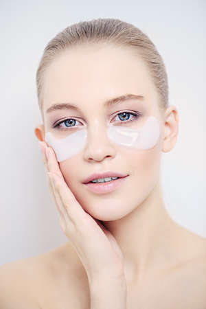 Close-up portrait of a beautiful young woman with collagen pads under her eyes. Spa, eye skin care. Foto de archivo - 102584767