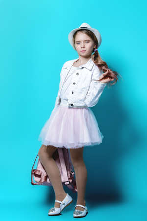Children's fashion. Cute nine year old girl with long blonde hair posing in summer clothes and a bag. Studio shot. Full length portrait. 免版税图像