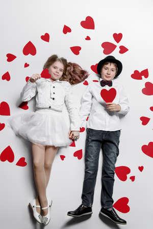 Heureux garçon et fille pré-ado posent entouré de coeurs. Amitié. Premier amour. La Saint-Valentin. Banque d'images