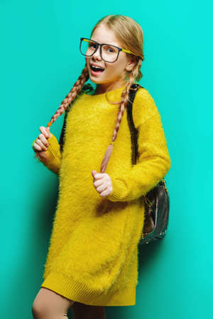 Cute nine year old girl posing in studio in fluffy yellow dress over blue background. Children's beauty and fashion.