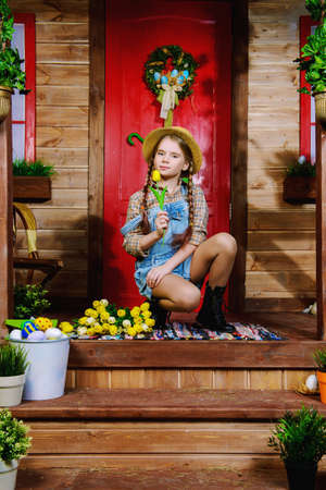 Easter holiday. Happy  pre-teen girl with a bouquet of spring flowers is sitting on the porch near the wooden house. Rural style, easter decoration. Banque d'images