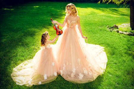 Classical music. Beautiful fairy girl teaches to play the violin a little girl. Musical fairy tales. Фото со стока - 102875938