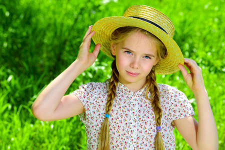 Pretty girl in a light summer dress is standing in a field in the countryside. Archivio Fotografico