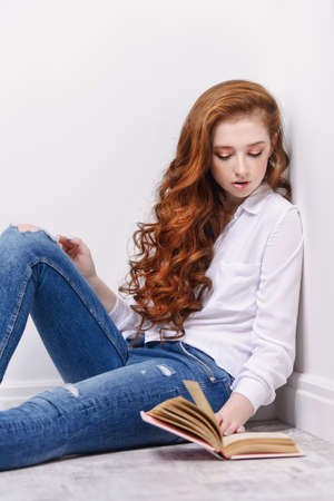 Beautiful red-haired teen girl wearing in jeans and blouse reading a book. Beauty, fashion. 版權商用圖片