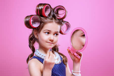 Portrait of a pretty little girl with curlers in her hair girl does make-up. Studio shot over pink background. Kids fashion.