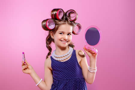 Portrait of a pretty little girl with curlers in her hair girl does make-up. Studio shot over pink background. Kid's fashion.