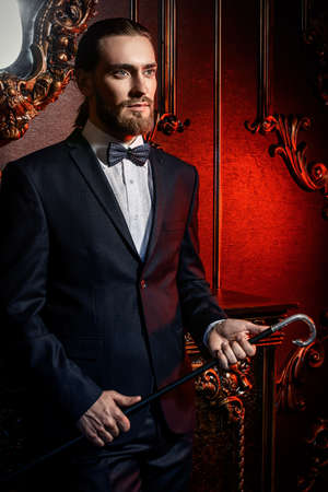 Portrait of a well-dressed imposing man in elegant suit posing in apartments with luxurious classic interior. Mens beauty, fashion. Hair styling, barbershop.  Stock fotó