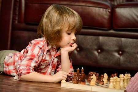 Little boy playing chess at home. Games and activities for children. Family concept. 版權商用圖片