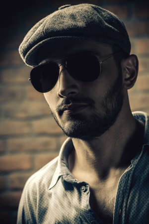 Portrait of a handsome man in a cap and sunglasses over brick wall background. Mens beauty, fashion. Mens barbershop. 스톡 콘텐츠