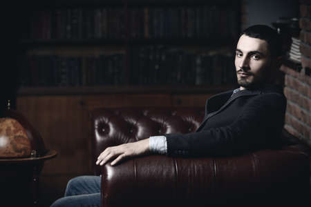 Portrait of a sexy handsome man on a leather sofa. Fashion shot. Mens beauty, fashion. Mens barbershop, Hairstyle.