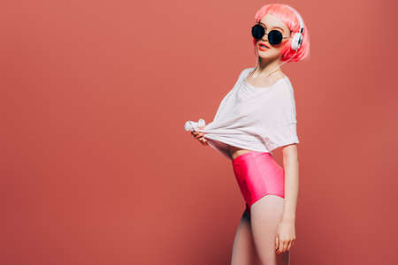 Trendy girl with pink hair wearing sunglasses enjoys the music on headphones. Pink background. Youth style, leisure. Standard-Bild - 103129056