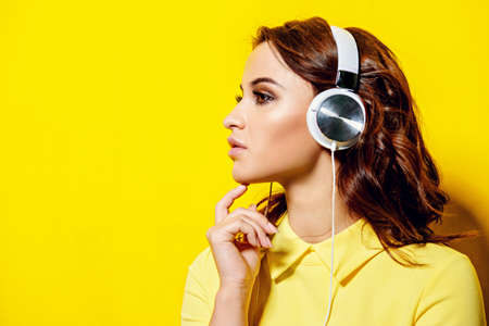 Modern girl enjoys listening to music in headphones. Leisure. Copy space.