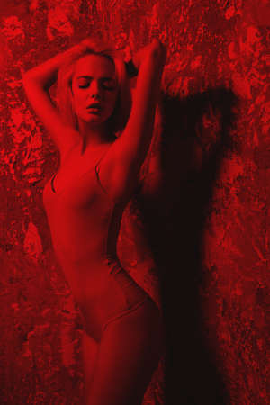 Attractive young woman in flesh-colored bodysuit posing in studio in red light. Beauty, fashion. Reklamní fotografie