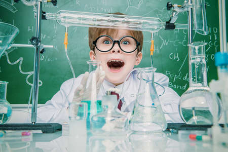 Funny school boy scientist in the laboratory. Educational concept.