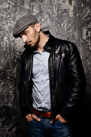 Portrait of a handsome man in a cap and leather jacket on a grunge background. Studio shot. Mens beauty, fashion. Mens barbershop. 스톡 콘텐츠