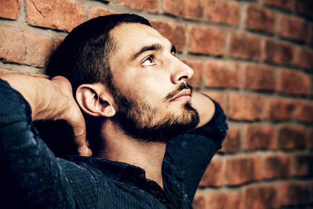 Portrait of a handsome brunet man standing by a brick wall. Mens beauty, fashion. Mens barbershop, Hairstyle. 스톡 콘텐츠