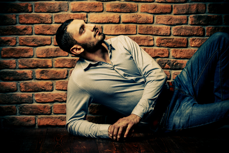 Portrait of a handsome brunet man posing by a brick wall. Mens beauty, fashion. Mens barbershop, Hairstyle.