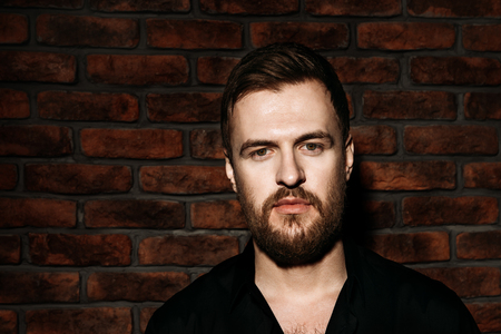 Fashion shot of a stylish brutal bearded man posing in black shirt. Studio shot over brick wall.