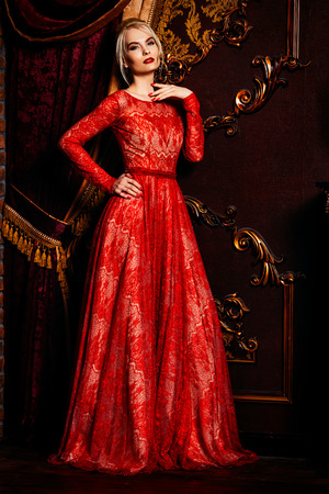 Attractive young woman in evening red dress stands in a luxury apartment. Classic vintage interior. Beauty, fashion. Evening makeup and hairstyle. Stok Fotoğraf