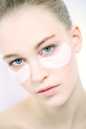 Close-up portrait of a beautiful young woman with collagen pads under her eyes. Spa, eye skin care.