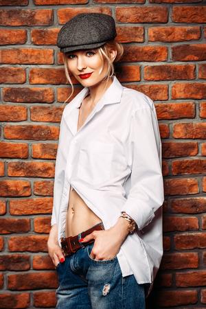 Portrait of a sexual young woman wearing white shirt and cap. Beautiful smart girl. Beauty, fashion.