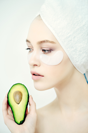 Beautiful spa woman with collagen pads under her eyes and avocado. Beauty, natural cosmetics concept. Spa, body care.