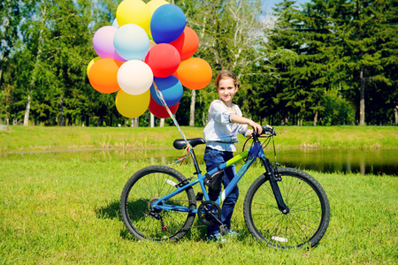 Happy girl is riding a bicycle with colored balloons in a park. Summer holidays. Birthday. 写真素材 - 103830687