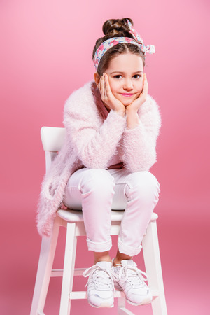 Childrens fashion. Cheerful seven year old girl wearing pink cardigan posing over pink background. Studio shot.