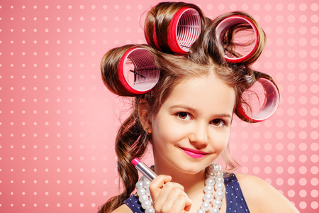 Portrait of a pretty little girl with curlers in her hair holding lipstick. Studio shot over pink background. Kid's fashion.