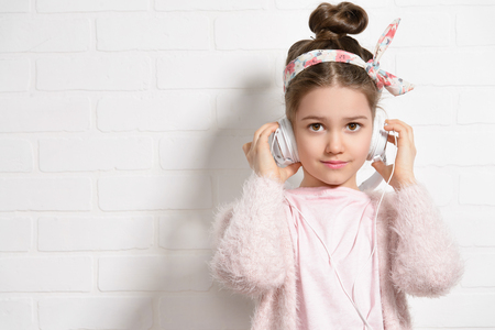 Childrens fashion. Pretty little girl wearing modern clothes listening to music on headphones near a white brick wall. Studio shot.