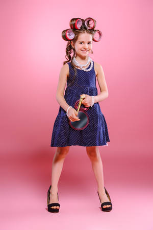 Portrait of a pin-up little girl with curlers in her hair in mother's shoes. Studio shot over pink background. Kid's fashion.