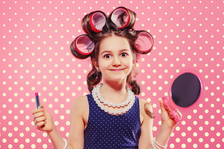 Portrait of a pretty little girl with curlers in her hair holding lipstick and mirror. Studio shot over pink background. Kid's fashion. Stockfoto