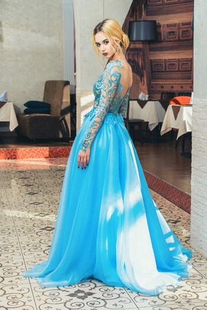 Gorgeous young woman posing in restaurant dressed in evening or wedding chic gown. Full length portrait. Beauty, fashion.