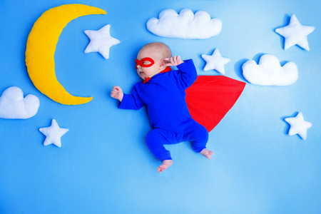 Little baby superhero with red cape flies through the night sky. Stockfoto