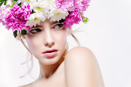 Portrait of a sensual spring lady in a wreath of flowers. Beauty, cosmetics. Copy space. Make-up. White background.
