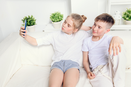 Happy joyful children are making selfie at home. Children's fashion. Modern lifestyle. Family concept.