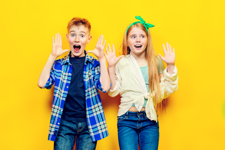 Portrait of two emotional children on a bright yellow background.