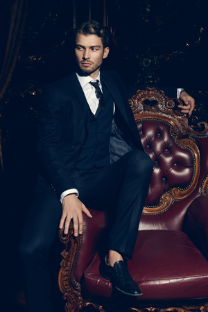 Imposing well dressed man in a luxurious apartments with classic interior. Luxury. Mens beauty, fashion. Imagens