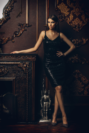 Portrait of an attractive young woman in tight black dress in a luxury apartment. Classic vintage interior. Beauty, fashion. Stock Photo