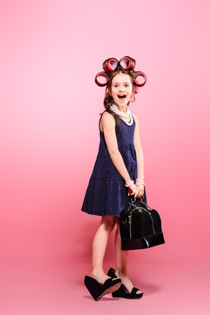 Portrait of a funny little girl with curlers in her hair in mother's shoes and bag. Studio shot over pink background. Kid's fashion. Stockfoto