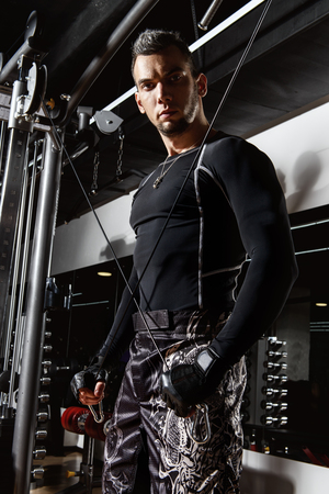 Muscular brutal man doing exercises in a gym. Health and sports concept. Banco de Imagens
