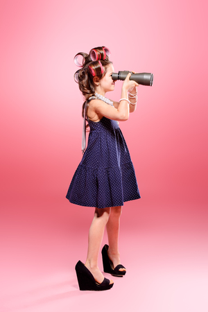 Pretty child girl looks through binoculars at something over pink background. Pin-up style. 스톡 콘텐츠
