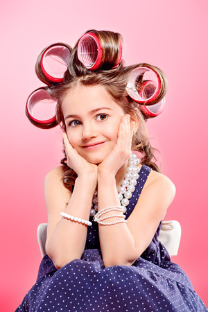 Portrait of a pretty little girl with curlers in her hair. Studio shot over pink background. Kids fashion. 写真素材