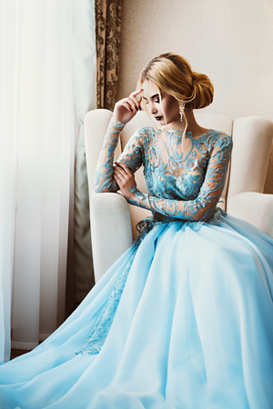 Portrait of a beautiful young woman in elegant blue dress. Luxurious apartments.