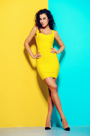 Beauty, fashion shot. Beautiful slender tanned girl in a yellow dress on a blue and yellow background. Brunette hair.