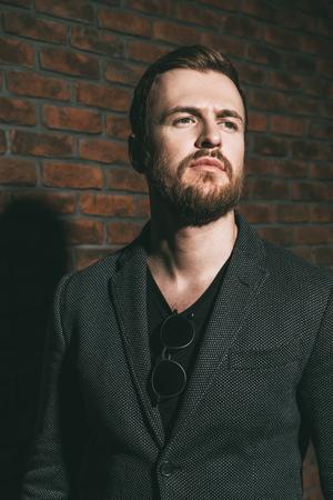 Fashion shot of a stylish brutal bearded man posing in gray jacket. Studio shot over brick wall. Stock Photo