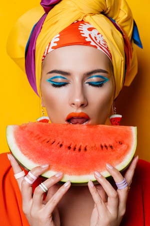 Fashionable woman with bright make-up eating watermelon. Yellow background. Beauty, fashion, make-up concept.