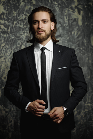 Fashion shot. Handsome young man posing in elegant suit over dark background. Mens beauty, fashion.