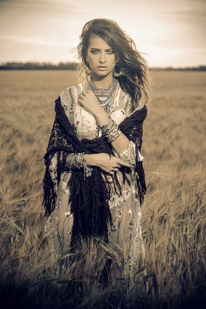 Fashion female model posing in a field. Contemporary bohemian style. Zdjęcie Seryjne